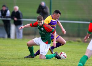 Ricky Fox of the Wexford Football League skips around the challenge of Mayo's Seáwn Morrissey during the last 16 tie in New Ross