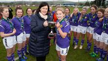 Fiona Ryan is presented with the trophy as her delighted team-mates look on