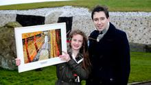 Simon Harris TD, Minister of State with special responsibility for the Office of Public Works, with Amber Hogan age 12 from Hollywood National school with her winning art work