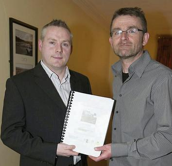 Jason Mullhall receiving the Blessington Tidy Towns five-year plan from Billy Flynn of Flynn Furney Environmental Consultants.