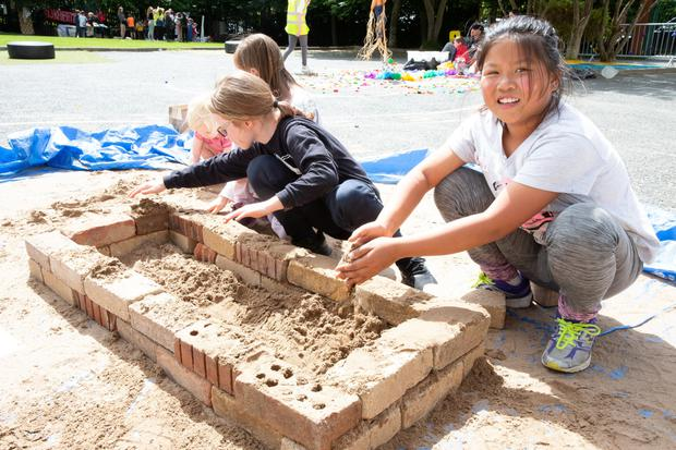 Willow Murphy Cardin and Anson Lau try some brick laying at the Bray School Project Art Day