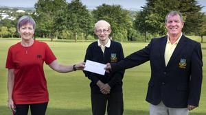 Terri Kenny of Baltinglass Tidy Towns is presented with the cheque by Tom Hannifin and captain of the golf club Michael O'Neill.