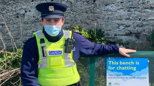 Garda Eanna Whelan trying out the chatting bench in Wicklow