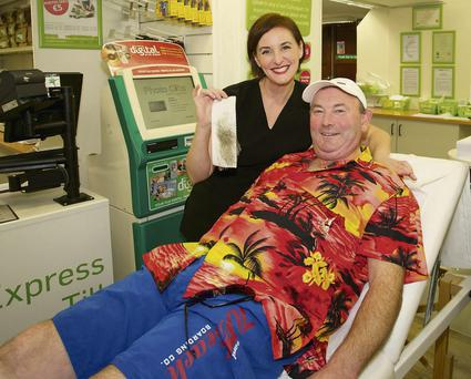 Derek Dunne the Butcher with Susan Fox (Eden Beauty) getting his legs waxed at Lloyd's Pharmacy in aid of Wicklow Cancer Support. Picture: Tim Thornton