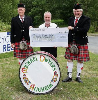 Denis Newsome and Mick O'Brien from the Michael Dwyer's Pipe Band Aughrim receiving a cheque for €1,478 from Myles Doyle from Avoca Recycling Centre