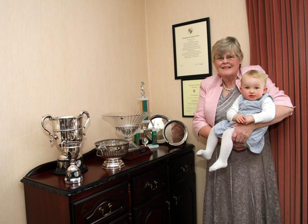 Muriel Hobson cradles her grandaughter, Laura beside her impressive trophy collection . Photo Joe Byrne