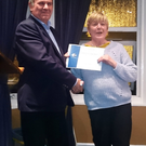 Tall Tales winner Carolann Murphy is presented with her certificate by head judge Colin Byford