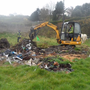 A mini-digger cleans up rubbish dumped at Ballyguile