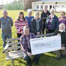 Dominic Nolan and Mick Furlong (seated) receive a cheque for 1600 Euro for Clonmore Cancer Society, the proceeds of The Golden Girls Fundraiser Back row - John Berminghan, Theresa Mannering, Liam O'Rourke, Anne Byrne, Colm O'Rourke, Kathleen O'Neill and Ann O'Rourke