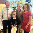Carnew NS pupil Conor Neville receiving a presentation from principal Kevin O' Donnell for full attendance throughout his primary school education. Pictured with them are his parents Ian Neville and Noelle O' Connor