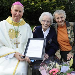 Sr Rita Clare receiving the President's letter from Bishop Denis Brennan. Also pictured is Sr Miriam Kerrisk