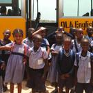 Pupils of Bugisi English Medium OLA Primary School beside the new bus