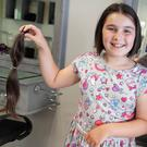 Niamh Farrell (10) from Arklow with hairdresser Benita Kavanagh and the hair she had chopped off to help the Rapunzel Foundation