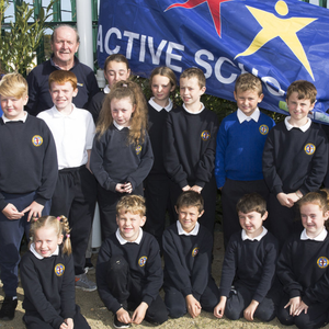 Teachers from the committee Ms Maguire and Ms McConn, Jim O'Riordan, Canon Sean Smith and Principal Carmel Dempsey with the students of the committee at the raising of the Active Flag at Newtownmountkennedy Primary School
