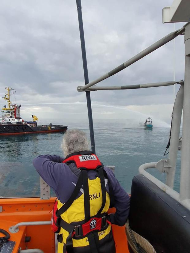 An RNLI crew member watches on as a tug attempts to extinguish the fire on the trawler. PHOTO BY RNLI/NUALA MCALOON