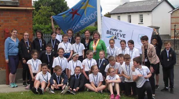 Pupils,teachers and Aisling Beacom (centre in green) with their Active Flag and Dare to believe Flag