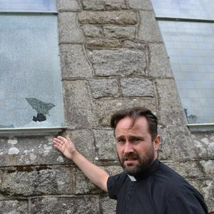 Rev Mairt Hanley with one of the damaged windows at St Mary's Church in Baltinglass
