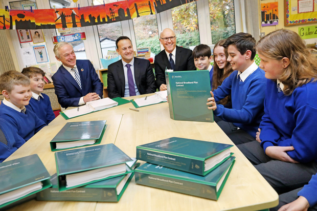(From left) Minister of Communications, Climate Action and Environment, Richard Bruton, An Taoiseach, Leo Varadkar and David McCourt with sixth class pupil Matthew McCoy as he reads the contract, alongside other pupils from St Kevins National School