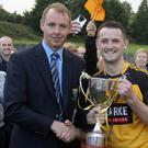 Wicklow County Board Vice Chairman Martin Fitzgerald presents the Darcy Sands IFC cup to Ashford captain Brendan Manning