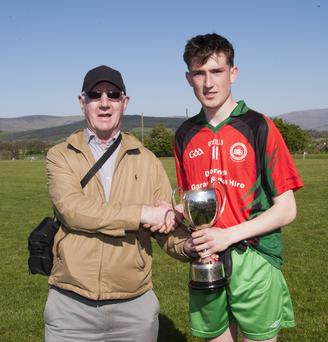 Schools Games Administrator Jim Murphy presents the cup to St Kevin's captain Aaron Kennedy.