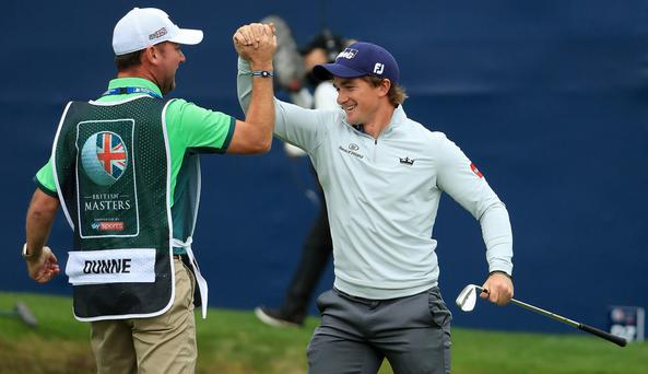 Greystones golfer Paul Dunne celebrates with his caddie, Bray's Darren Reynolds, after chipping in on the 18th hole to win the tournament during day four of the British Masters at Close House Golf Club on Sunday