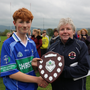 AGB captain Ross Kenny collects the trophy from Coiste na nÓg secretary Lucy Mooney