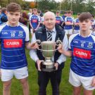 Éire Óg's joint captains Daire Devine and Fionn O'Carroll receive the cup from Coiste na nÓg chairman Pat Dunne