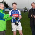 Éire Óg captain Eoghan McTague collects the Paudge Dooley Memorial Cup from Eugene Dooley with Wicklow GAA chairman Martin Fitzgerald.