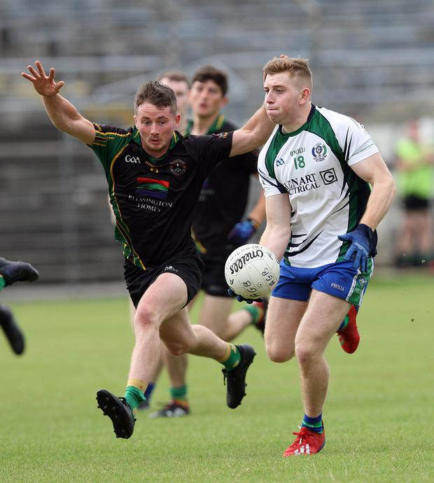 AGB's Darragh Fitzgerald looks to get a pass away as Hollywood's Conor Burke closes in