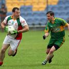 Pauric Keogh of Kiltegan is tracked by Vincent Flaherty of Annacurra during the Senior football championship match in Aughrim
