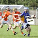 Armagh's Dylan Murray tries to halt the progress of Wicklow's Sean Germaine during the All Ireland minor 'B' hurling championship in Pearse's park, Arklow