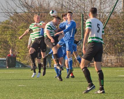 Andrew O'Brien of Greystones United looks on as Stephen Metcalfe and Jack Tanner challenge for the ball