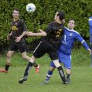 Robert Elliott of Carnew AFC and Danny Byrne of Ashford Rovers battle for possession.