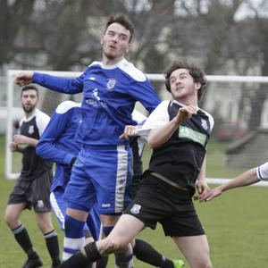 Anto Byrne of Ashford Rovers gets his head to the ball ahead of Evan Moran of Newtown United