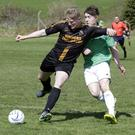 Justin House of Carnew AFC is tracked by Newtown's Ryan Cahill