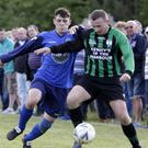 Nathan Watters of Glencormac United challenges Alan O'Neill of Arklow United.