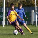 Niall Connolly of the Wexford Football League is tracked by Luke Kearney of the Wicklow Football League