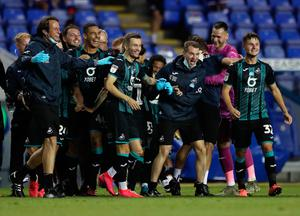 Swansea players celebrate after a 4-1 victory over Reading at the Madejski Stadium on Wednesday night which saw them qualify for the Championship play-offs. Photo: Naomi Baker