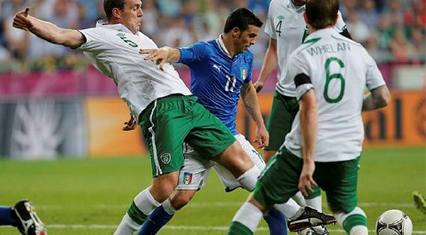 Ireland's Glenn Whelan (R) and John O'Shea watch as their team mate Richard Dunne (L) fights for the ball with Italy's Antonio Di Natale during their Group C Euro 2012 soccer match at the City stadium in Poznan.