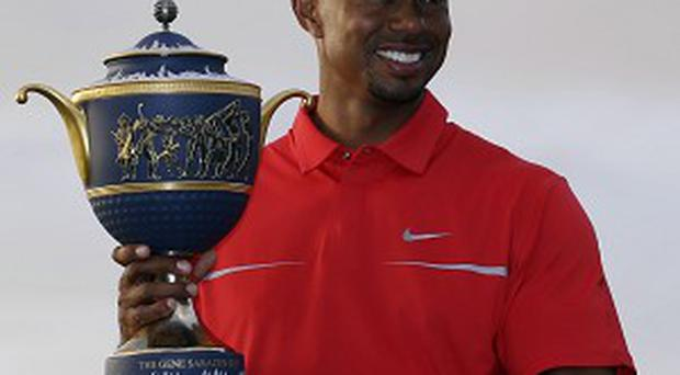 Tiger Woods poses with his trophy after winning by two shots