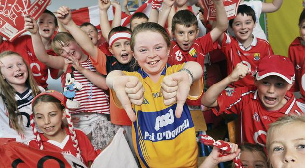 Clare supporter Maeve de Paor (9) stands tall in the midst of her Cork-supporting schoolmates in Gaelscoil Ui Riordain, Ballincollig, ahead of the All-Ireland hurling final on Sunday