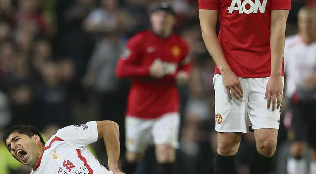 Luis Suarez reacts to being tackled by Phil Jones of Manchester United at Old Trafford last night