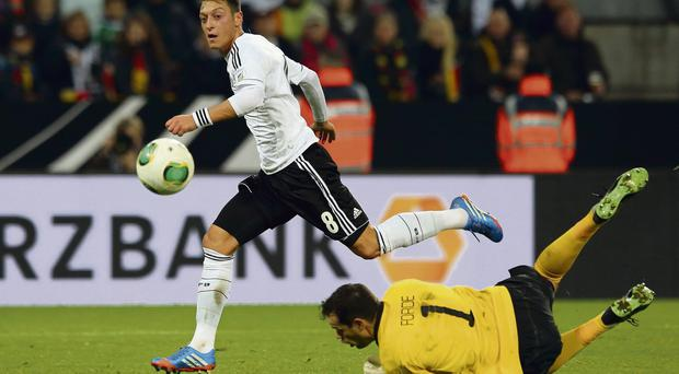 Mesut Ozil chips the ball over David Forde to score Germany's third goal against Ireland in Cologne last October