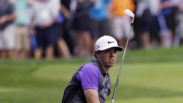 Rory McIlroy had been delayed, before finding his overnight lead evaporate (AP)