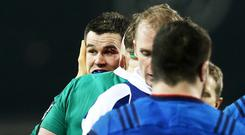Johnny Sexton, left, receives treatment for the cut eye from performing a choke tackle