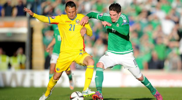 Northern Ireland's Kyle Lafferty and Romania's Dragos Grigore (left) battle for the ball during the UEFA European Championship Qualifying game at Windsor Park, Belfast.