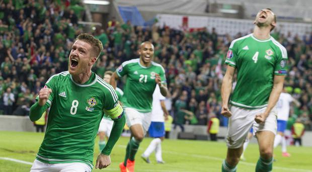 Steven Davis, pictured left, scored twice against Greece as Northern Ireland booked their place at Euro 2016
