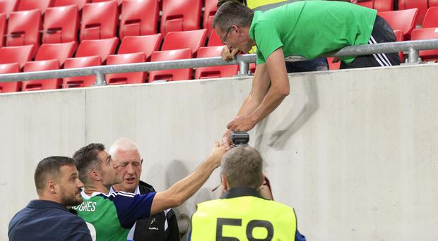 Northern Ireland's Aaron Hughes greets a fan after the match against Slovakia