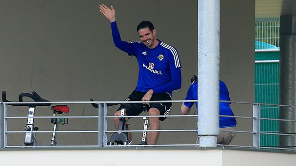 Kyle Lafferty waves on an exercise bike at training on Wednesday
