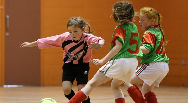 Lea Shannon from Clonguish, Longford, takes on Shauna Burke and Clodagh Acton from Kilmaine, Mayo, during the Girls U10 Indoor Soccer play-off.